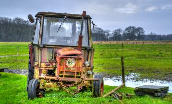 Yellow Farm Equipment on Green Grass Field