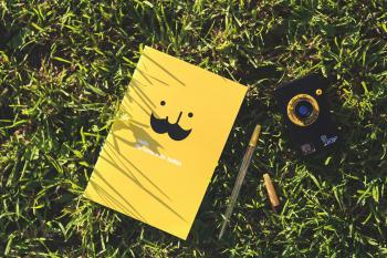 Yellow notebook on the grass