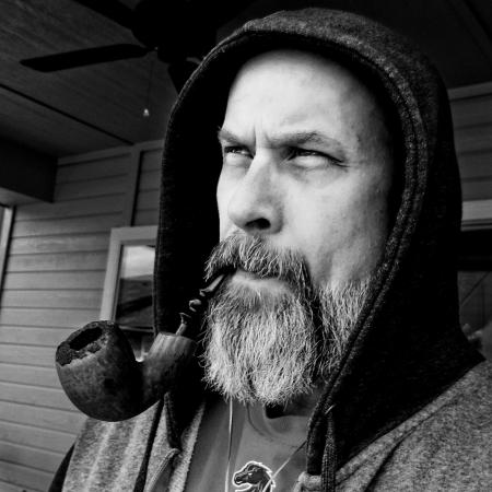 A brutal man with a beard smokes a pipe with tobacco