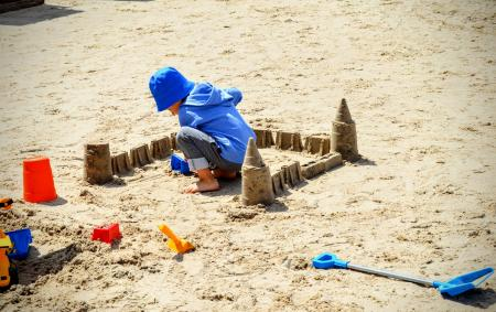 A child plays with sand, sculpting a sand castle on a sandy beach
