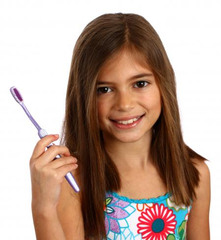 A pretty young girl holding a toothbrush