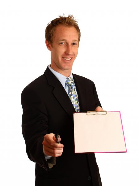 A young businessman holding a clipboard