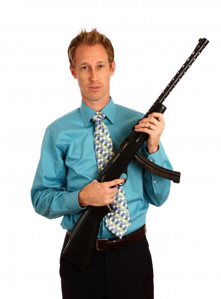 A young businessman holding a rifle