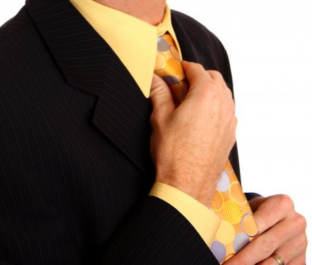 A young businessman in a suit adjusting