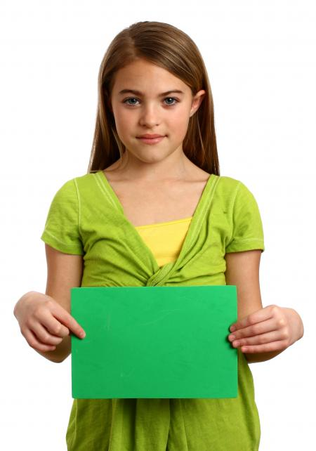 A young girl holding a blank sign
