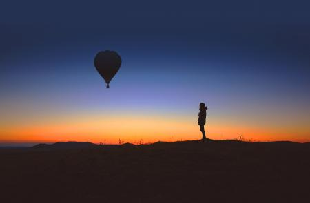 Alone person observes an hot air balloon at sunrise