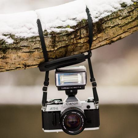 Black and Gray Canon Dslr Camera Hanging on Brown Tree Trunk With Snow