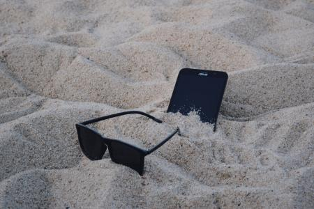 Black Wayfarer-style Sunglasses Beside Black Asus Android Smartphone on Brown Sand