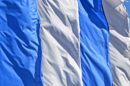 Blue and white flags are blowing softly in the wind.