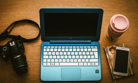 Blue Hp Netbook Beside Black Nikon Dslr Camera and White Samsung Smartphone on Book