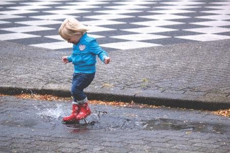 Boy in Blue Jacket Hopping on Water Puddle