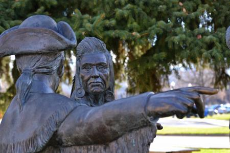 Bronze statue of a man in a cocked hat and an old woman