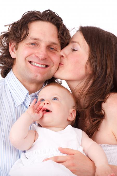 Brown Haired Woman Kissing Man in Blue White Dress Shirt Holding Baby in White Dress