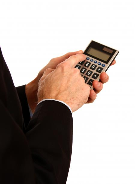 Businessman in a suit using a calculator
