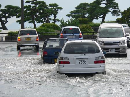 Cars driving on a flooded street in Matsue, Japan