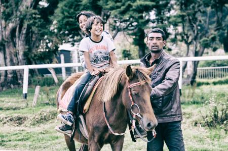 Children Riding Horse With Adult Guiding