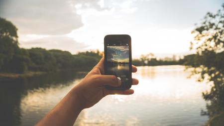 Close-up of Hand Holding Mobile Phone Against Lake