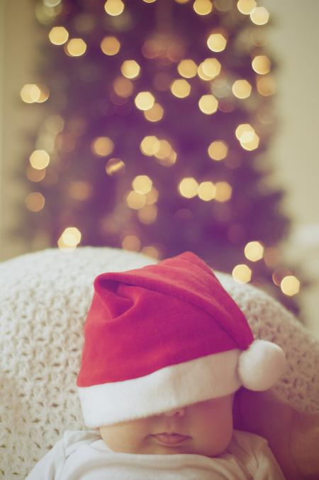 Close-up of Illuminated Christmas Tree And A Baby
