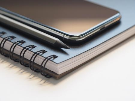 Closeup Photo of Black Smartphone Near Black and Grey Pencil on Black Spiral Notebook