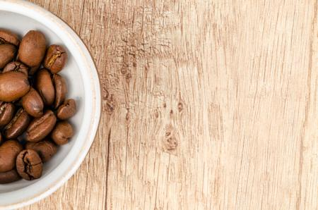 Coffee Beans on White Ceramic Bowl on Top of Brown Wooden Surface