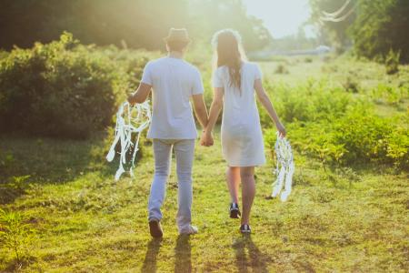 Coupe With White Dress and Suit Holding a White Dreamcatcher While Walking on Green Grass