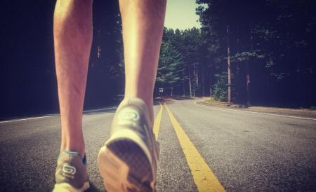 Feet of an athlete running on a deserted road