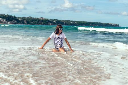 Female Sitting on Beach Shore Wearing White Shirt
