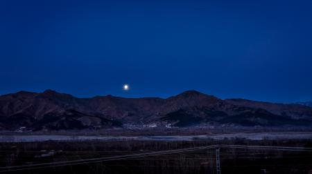 Full Moon Above the Mountain Ranges Near Town
