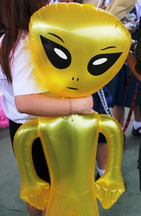 Girl holds an inflatable alien toy