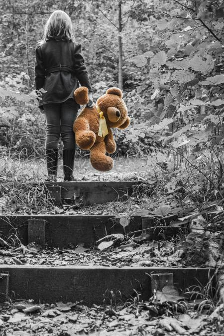 Girl in Jacket Carrying Brown Bear Plush Toy Selective Color Photo