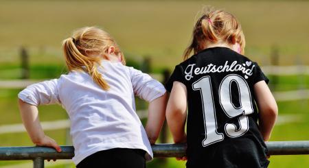 Girl in White Long Sleeve Shirt Beside Girl in Black T Shirt Holding Black Metal Handrail at Daytime