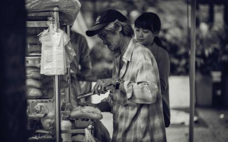 Grayscale Photo of a Man Selling Sandwiches on the Streets