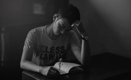 Grayscale Photography of Man in Shirt Reading Notebook