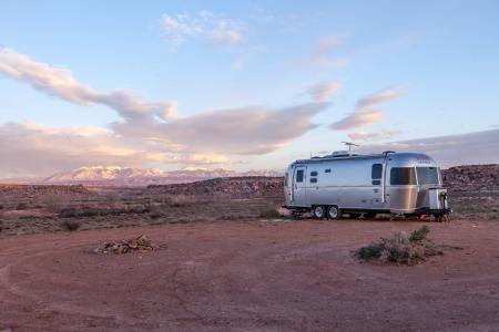 Grey and Black Recreational Vehicle on Ground Under Blue and White Sky