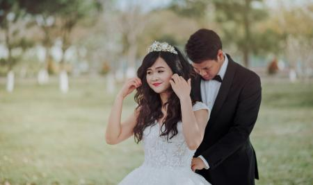Groom Tying Bride's White Lace Wedding Gown at the Back