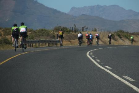 Group of bikers on the road behind the mountains