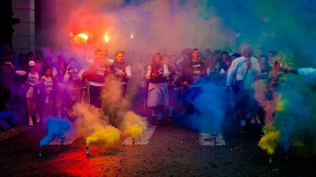Group of People on Road With Assorted-color Smokes