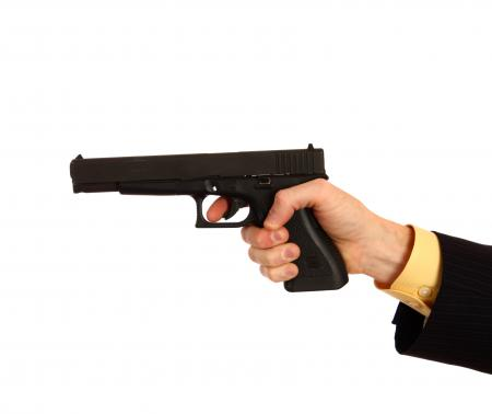 Hand in a business suit holding a pistol