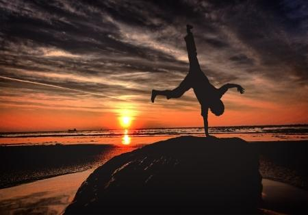 Handstanding on the beach at sunset - Youth and vitality