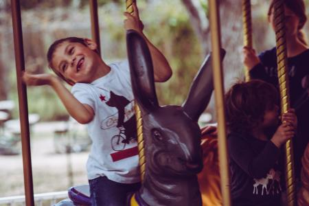 Happy child riding a rabbit carousel