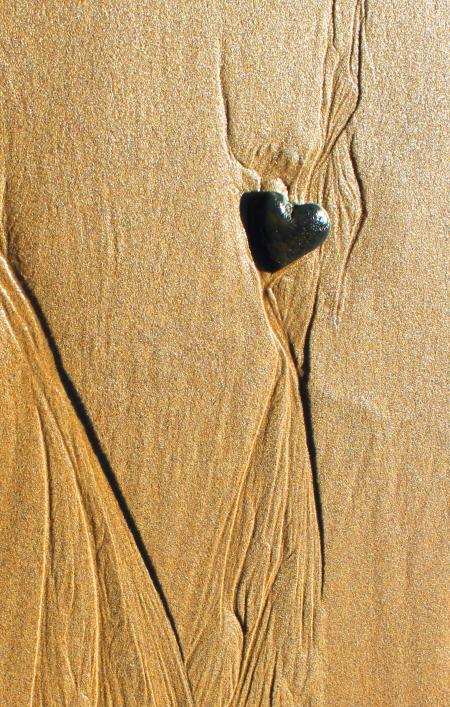 Heart-shaped pebble in the sand