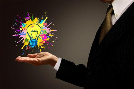 Ideas at Hand - Businessman and Painted Lightbulb