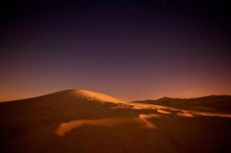Landscape of Sand Dunes at Dusk with Stars in Sky