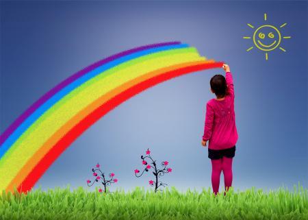 Little girl painting a rainbow on the sky