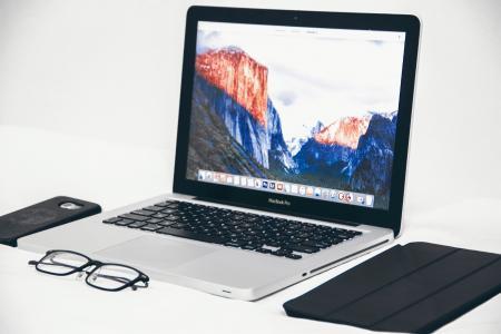 Macbook Air Beside Eyeglasses and Black Smart Case