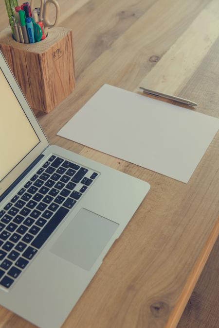 Macbook Air Beside White Paper and Click Pen on Top of Table