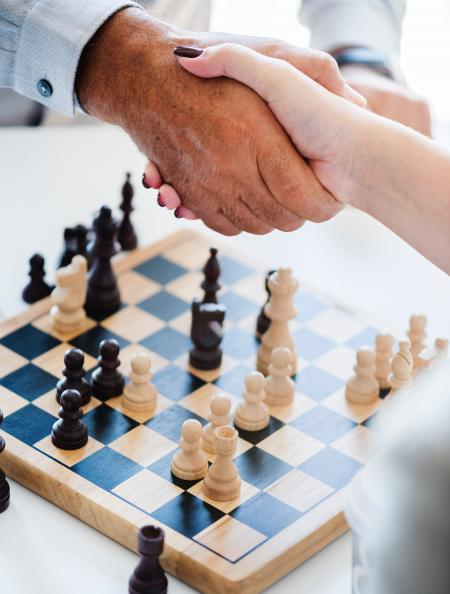 Man and Woman Shaking Hands over a Game of Chess
