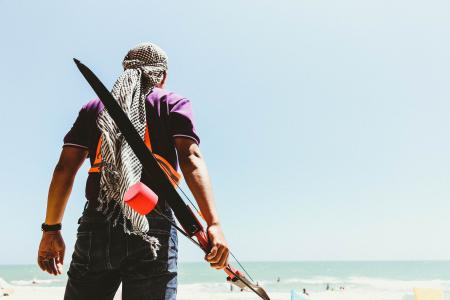 Man Holding Bow in Seashore