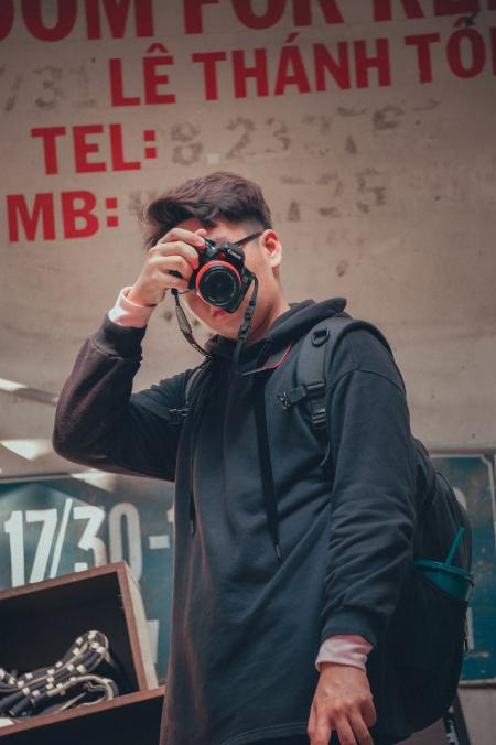 Man Holding Camera Beside Text Printed Wall
