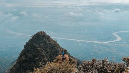 Man in Blue on Top of the Mountain With Areal View